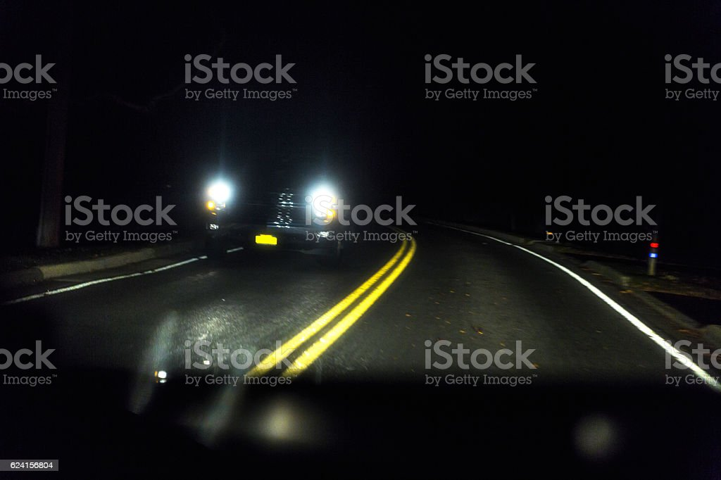 Approaching Vehicle Headlights on Rural Night Highway Curve stock photo