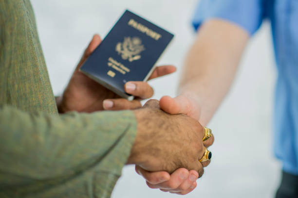 Approval A young Indian man is at the border, a customs officer is holding his passport, inspecting its authenticity and approving him for travel. citizenship stock pictures, royalty-free photos & images
