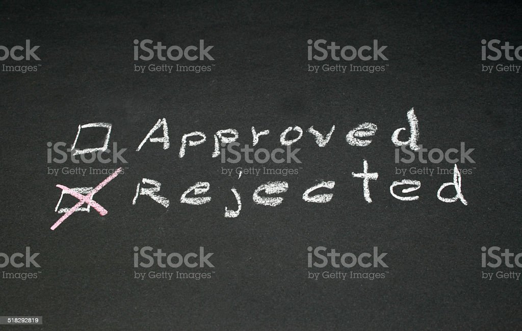 approved and rejected written with chalk on blackboard stock photo