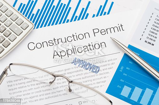 Approved Construction Permit Application with pen and calculator