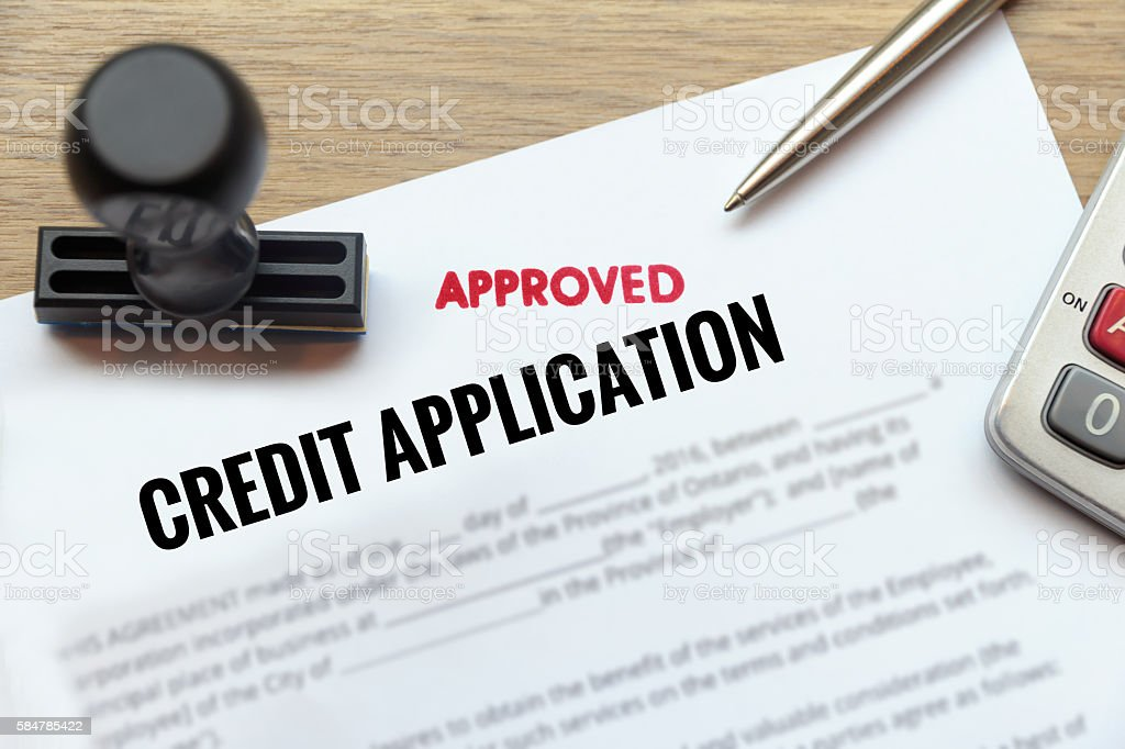 Approved credit application form lay down with rubber stamp stock photo