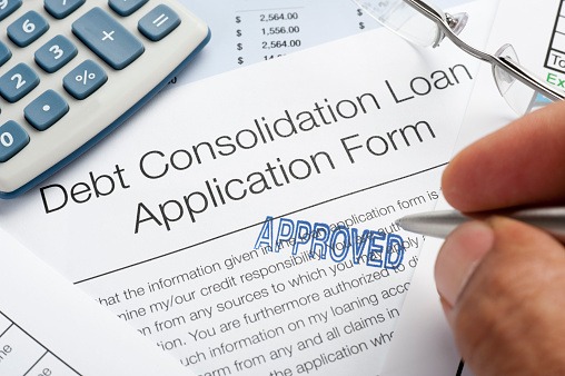 A close up picture focused on an Approved Debt Consolidation Loan Application Form. There is also a hand holding a grey pen. There are some glasses and a calculator next to the application form. The Approved letters are in blue and capital letters.