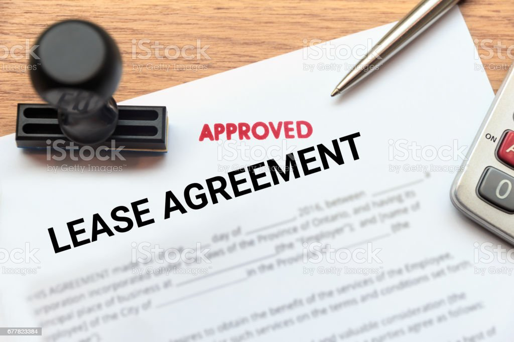 Approved lease agreement document with rubber stamp and calculator on wooden desk. stock photo