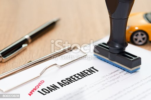 512011833istockphoto Approved loan agreement document with rubber stamp and car model toy on wooden desk. 806320628