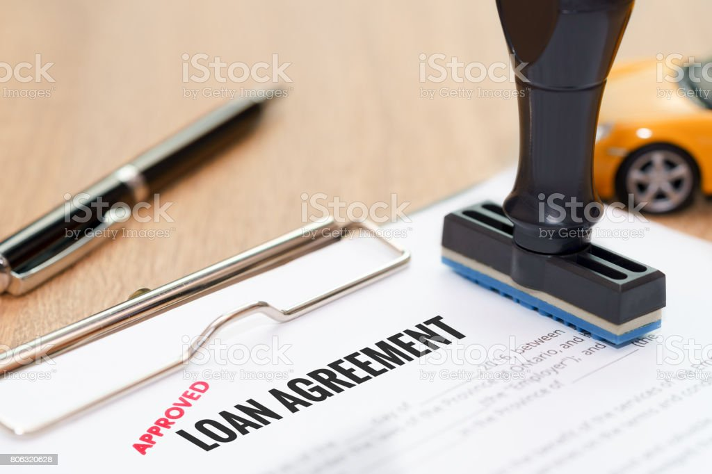 Approved loan agreement document with rubber stamp and car model toy on wooden desk. stock photo