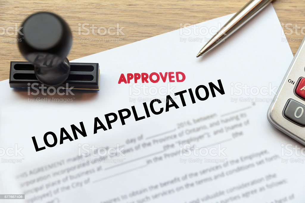 Approved loan application form lay down on  desk with stamp stock photo