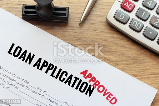 istock Approved loan application with rubber stamp and calculator 540112526