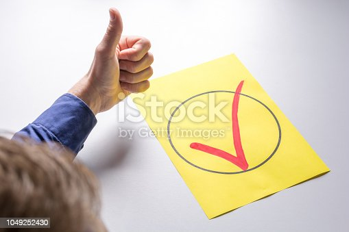 istock Approving gesture of a man in the office with approving tick 1049252430