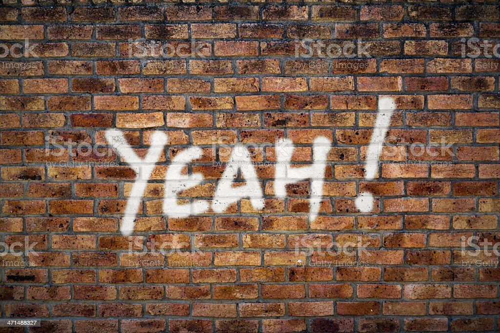 Approving graffiti on brick wall says YEAH! royalty-free stock photo