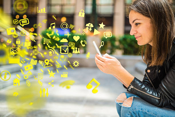Apps, media and other information flying around a smartphone stock photo