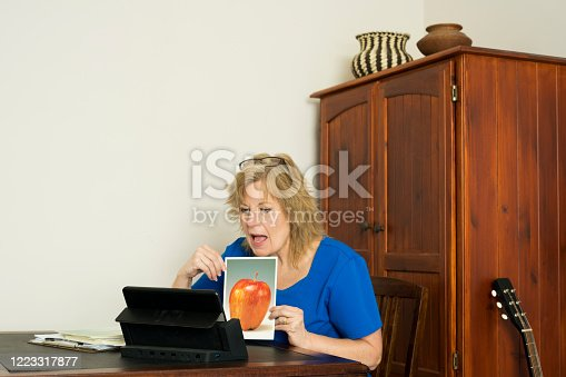 Blond female speech language pathologist, or speech therapist, wearing  royal blue scrubs provides teletherapy services by engaging with her patient online through her computer at home during the Covid-19 pandemic. Therapist is showing large single object pictures to elicit verbal responses that include naming for apraxia, word-finding for anomia, sentence descriptions for verbal expression.