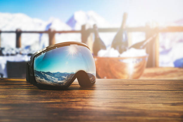 apres ski - goggles with mountains reflection on the restaurant table at ski resort stock photo