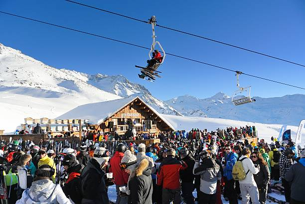 Apres Ski Val Thorens, France - January 22, 2013: People having a drink at the popular La Folie Douce bar at the ski piste near Val Thorens on a beautiful sunny day. Skiers are sitting in the overhead chair lift. apres ski stock pictures, royalty-free photos & images
