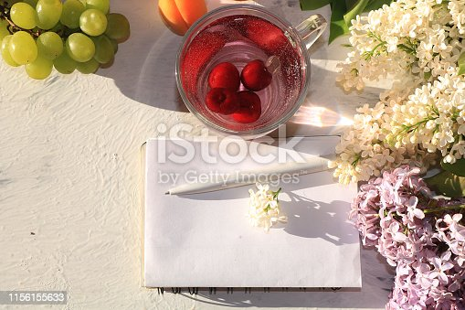 Apricot and cherry juice, apricots, cherries and grapes on a sunny table, top view, selective focus Summer drinks and fruits during a break with colored branches of lilac,