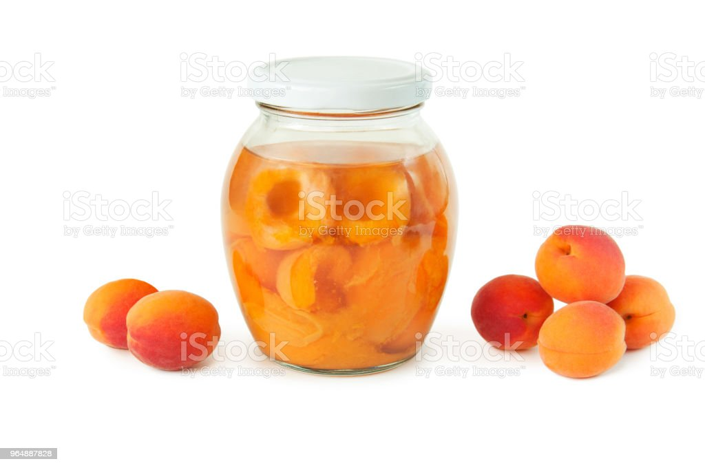 apricot compote in a glass jar and a bunch of ripe apricots on a white background. sweet and healthy dessert royalty-free stock photo