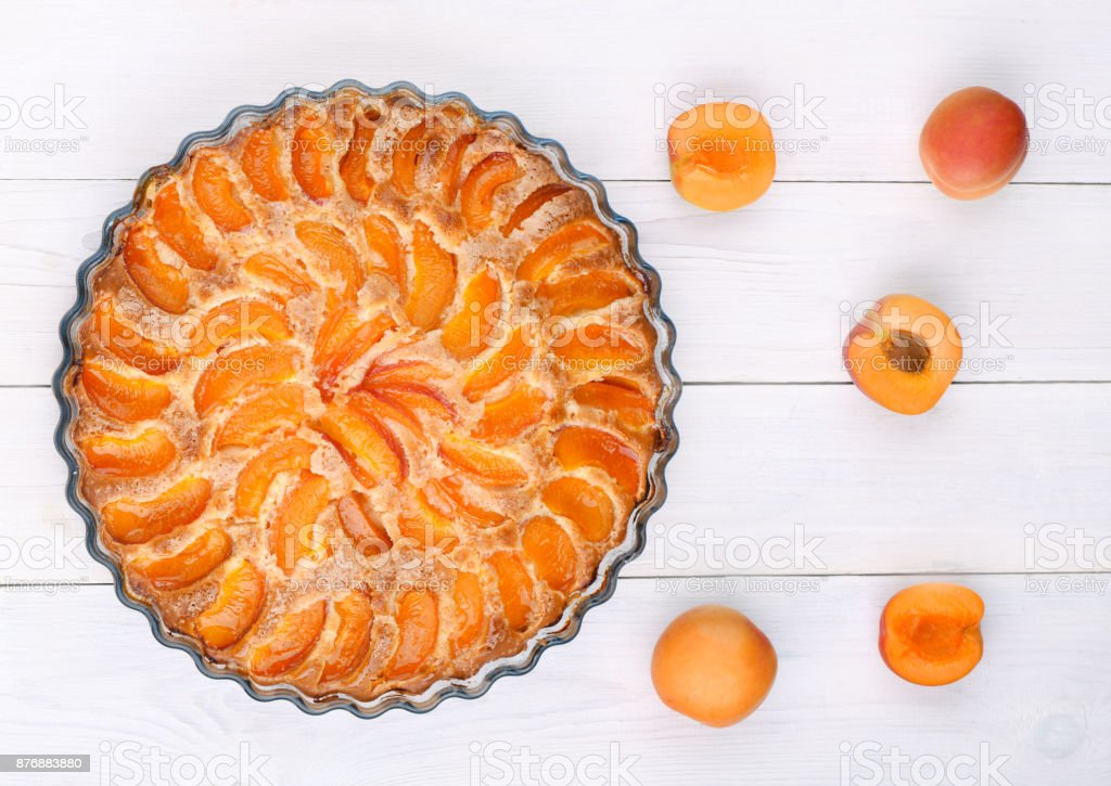 Apricot pie on a white wooden table, top view. stock photo