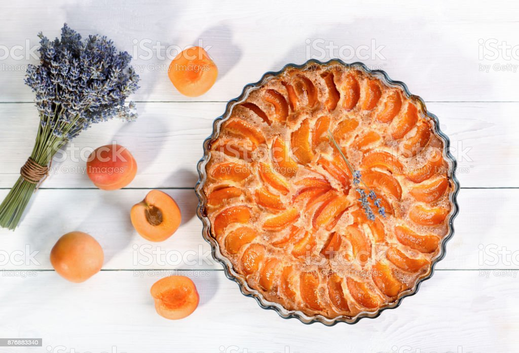 Apricot pie with a sprig of lavender and fresh fruit, top view. stock photo