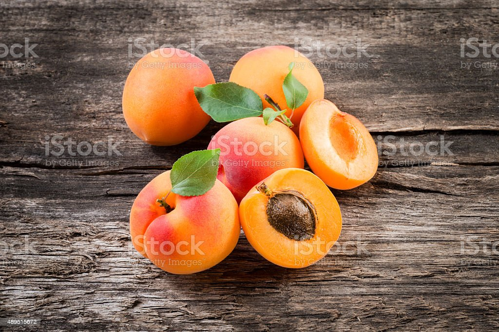 Apricot with leaves on wooden background stock photo