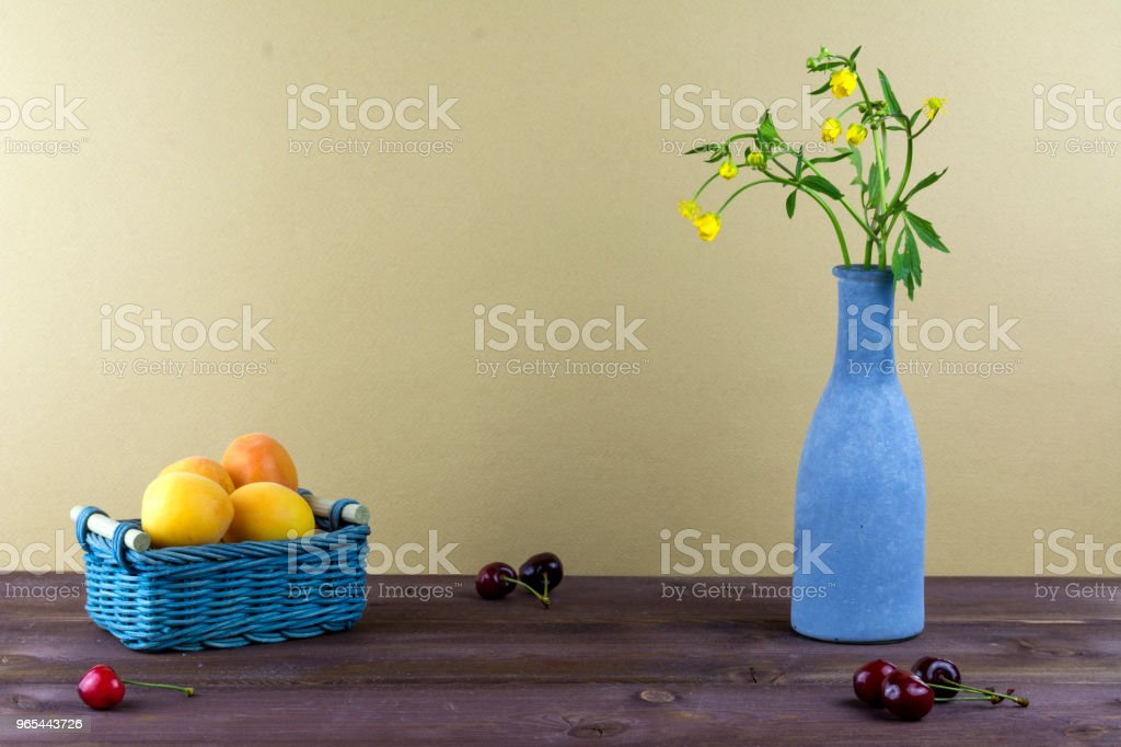 Apricots are in a wicker basket. Cherries are on a wooden table. Vase with wildflowers on a beige background. Summer mood royalty-free stock photo