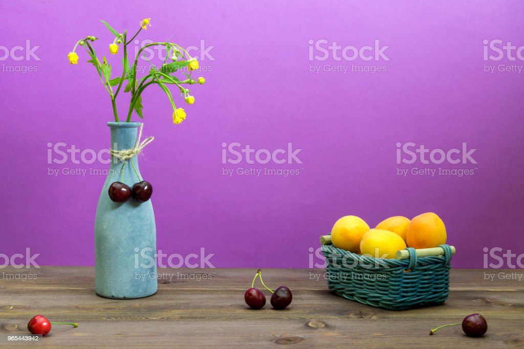 Apricots are in a wicker basket. Cherries are on a wooden table. Vase with wildflowers on a purple background. Summer mood - Zbiór zdjęć royalty-free (Bez ludzi)