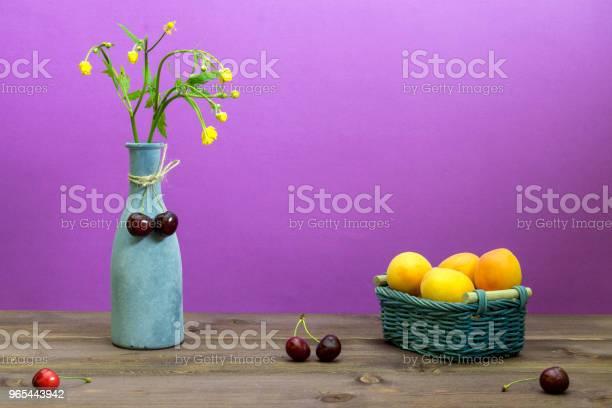 Morele Są W Wiklinowym Koszu Wiśnie Są Na Drewnianym Stole Wazon Z Polnych Kwiatów Na Fioletowym Tle Letni Nastrój - zdjęcia stockowe i więcej obrazów Bez ludzi