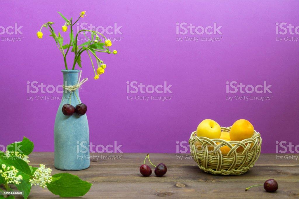 杏在柳條籃子裡。櫻桃在木桌上。紫色背景的野花花瓶。夏季心情 - 免版稅俄羅斯圖庫照片