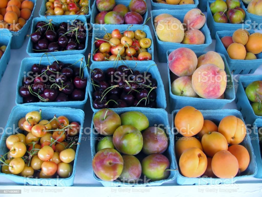 Apricots, cherries, peaches and plums at the market stock photo