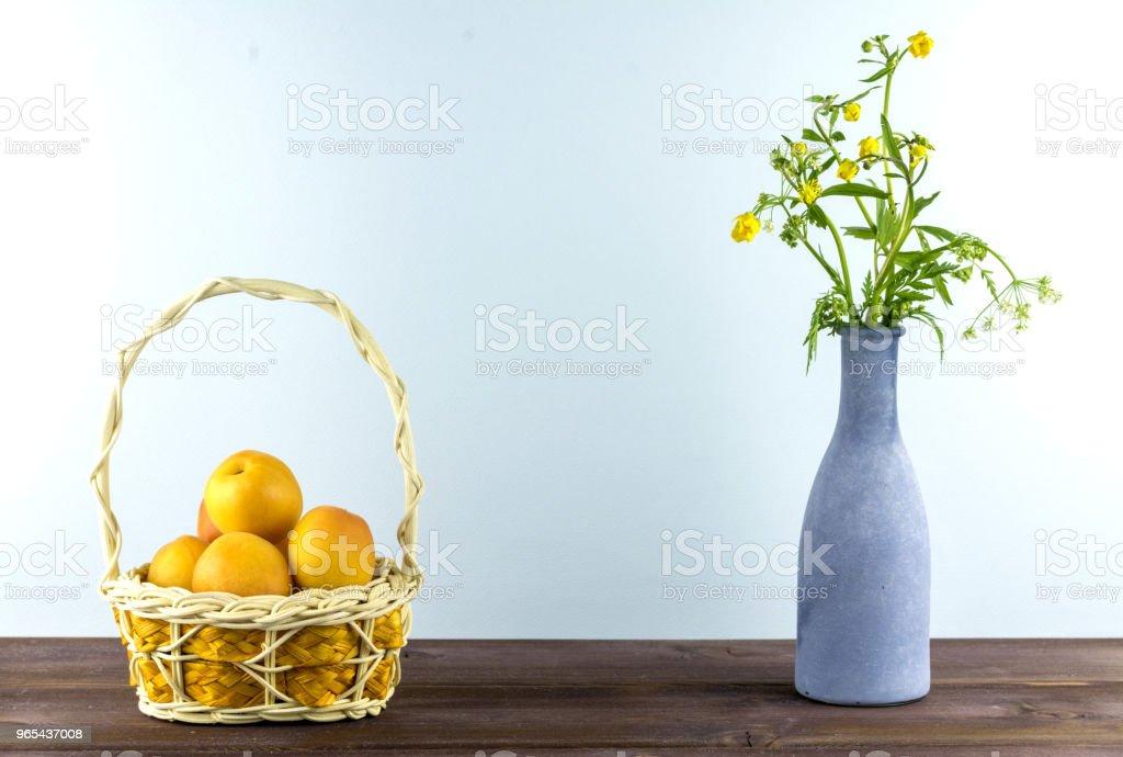 Abricots dans le panier. Vase avec fleurs sauvages sur un fond bleu. Humeur d'été - Photo de Abricot libre de droits