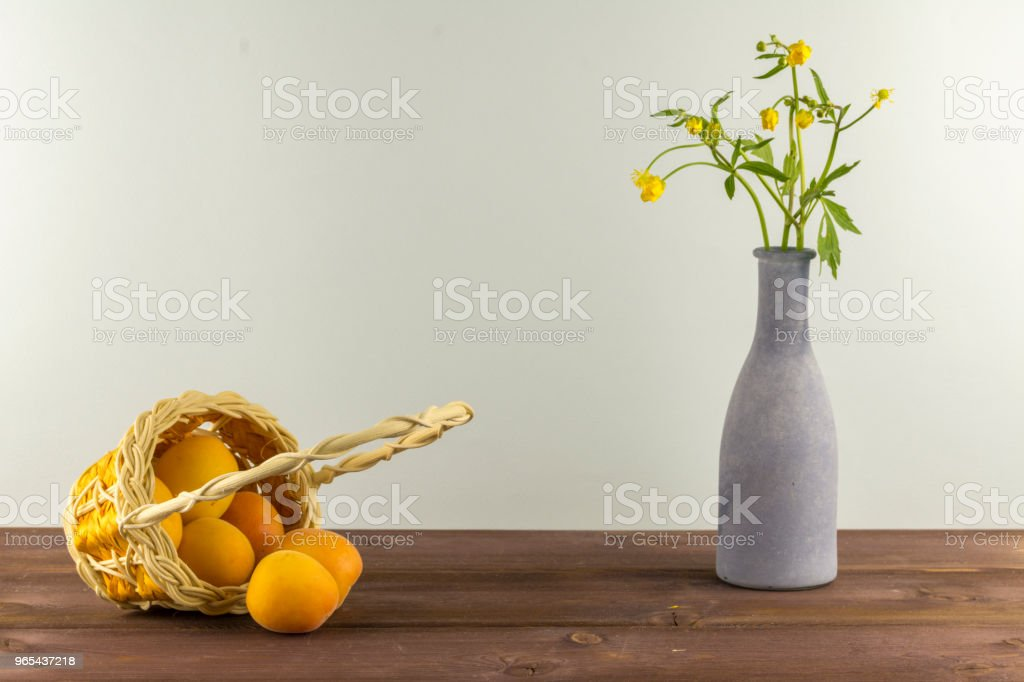 Apricots in the basket. Vase with wildflowers on a blue background. Summer mood zbiór zdjęć royalty-free