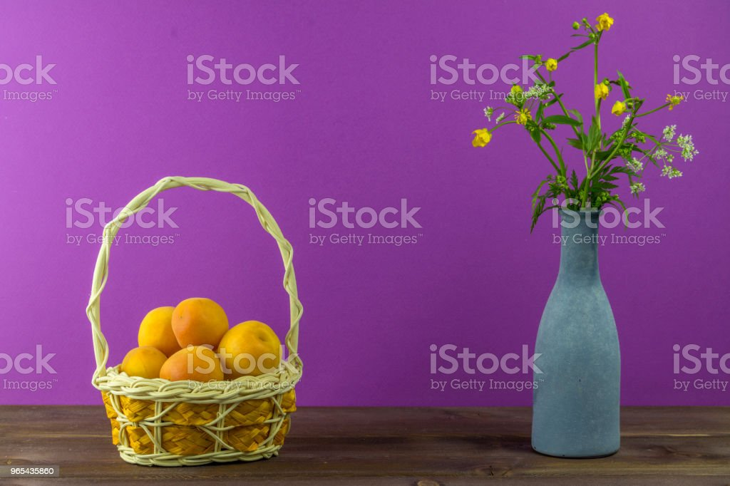 Apricots in the basket. Vase with wildflowers on a purple background. Summer mood royalty-free stock photo