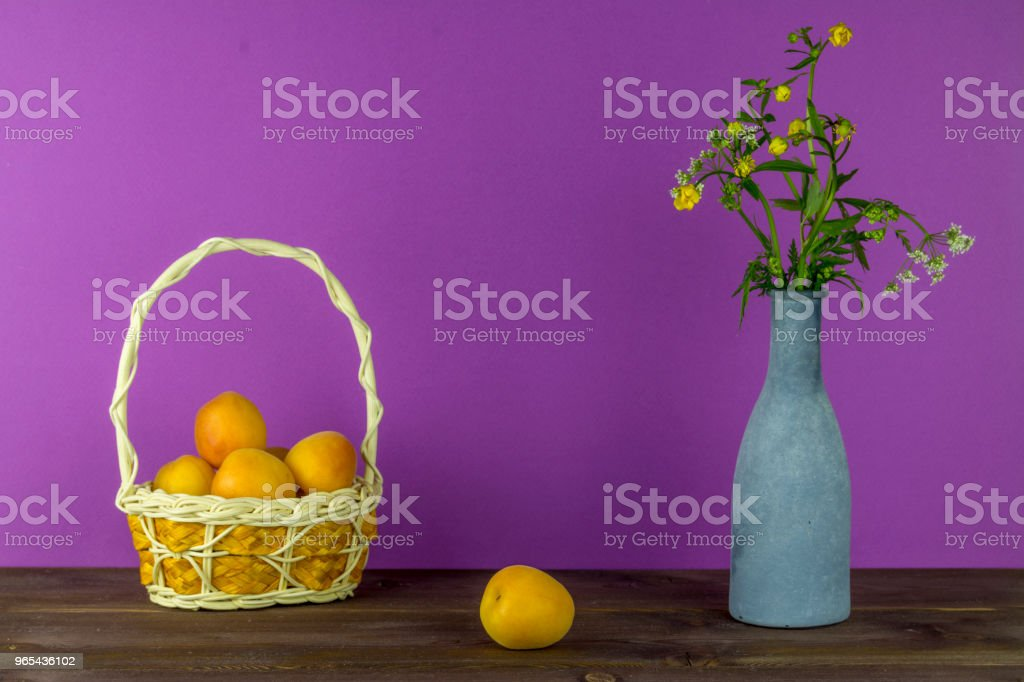 Apricots in the basket. Vase with wildflowers on a purple background. Summer mood zbiór zdjęć royalty-free