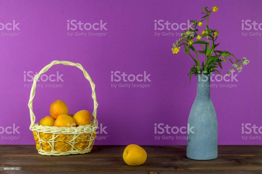 Abricots dans le panier. Vase avec fleurs sauvages sur un fond violet. Humeur d'été - Photo de Abricot libre de droits
