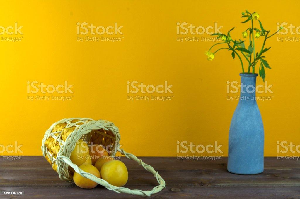 Abricots dans le panier. Vase avec fleurs sauvages sur un fond jaune. Humeur d'été - Photo de Abricot libre de droits