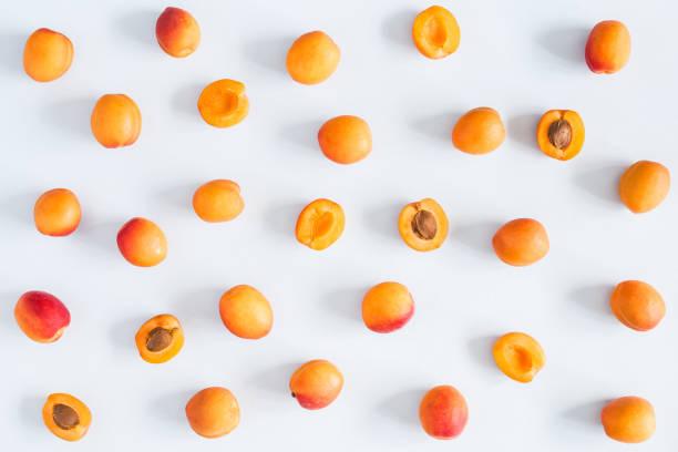 aprikosen auf pastell blau hinterlegt. flach legen, top aussicht - aprikose stock-fotos und bilder