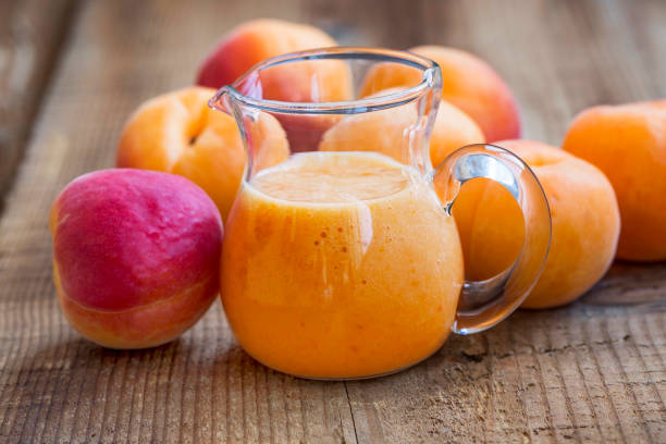 Apricots smoothie with fruits on wooden board stock photo