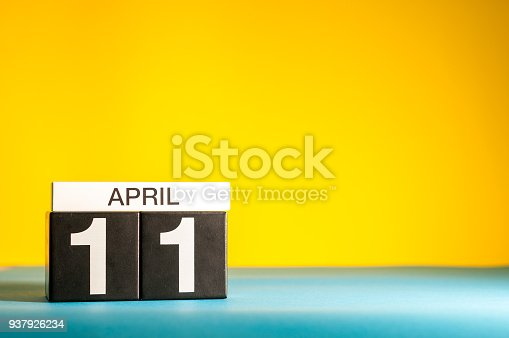 istock April 11th. Day 11 of april month, calendar on table with yellow background. Spring time, empty space for text 937926234