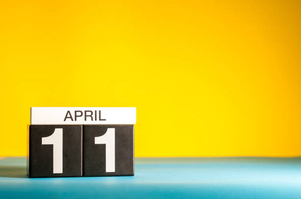 April 11th. Day 11 of april month, calendar on table with yellow background. Spring time, empty space for text stock photo