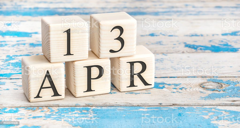 April 13th. Wooden cubes with date of 13 April  on old blue wooden background. stock photo