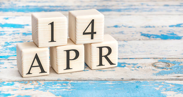 April 14th. Wooden cubes with date of 14 April  on old blue wooden background. stock photo