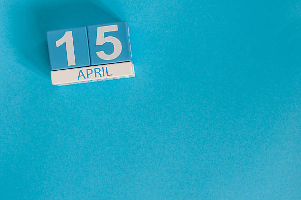 April 15th. Tax Day. Image of april 15 wooden color April 15th. Tax Day. Image of april 15 wooden color calendar on blue background.  Spring day, empty space for text. April stock pictures, royalty-free photos & images