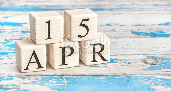 istock April 15th. Wooden cubes with date of 15 April  on old blue wooden background. 654353928