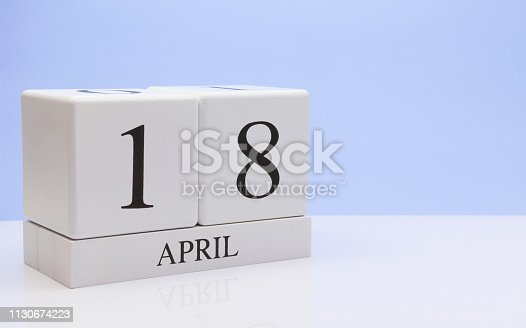 istock April 18st. Day 18 of month, daily calendar on white table with reflection, with light blue background. Spring time, empty space for text 1130674223