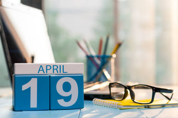 april 19th. day 19 of month, calendar on business office background, workplace with laptop and glasses. spring time, empty space for text - number 19 stock photos and pictures