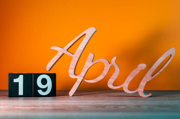 april 19th. day 19 of month, daily wooden calendar on table with orange background. spring time concept - number 19 stock photos and pictures