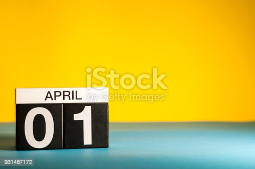 istock April 1st. Day 1 of april month, calendar on table with yellow background. Spring time, empty space for text 931487172