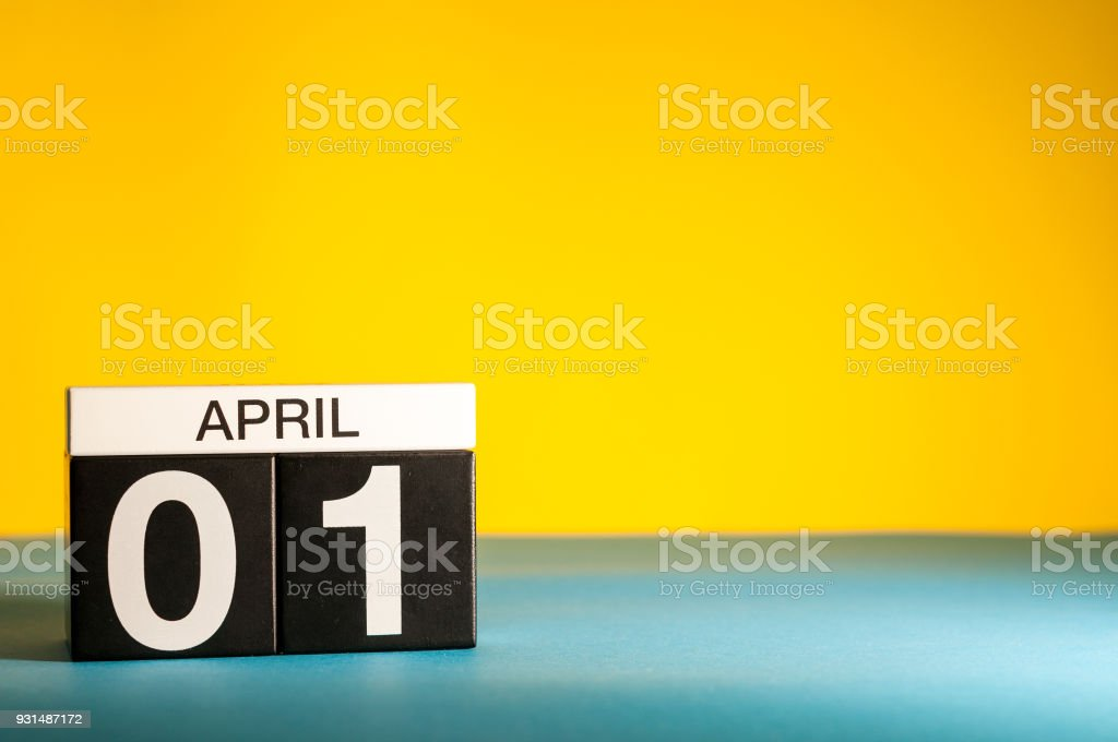 April 1st. Day 1 of april month, calendar on table with yellow background. Spring time, empty space for text stock photo