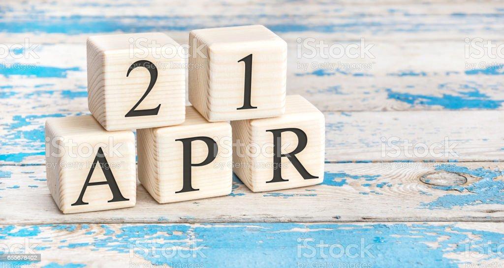 Am 21. April. hölzerne Würfel mit Datum vom 21. April auf alten blauen hölzernen Hintergrund. – Foto