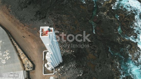 April 22, 2019: AERIAL. Unusual white lighthouse, which stands on the coast of volcanic origin. Lava froze, reaching the ocean. Tenerife, Canary Islands, Spain. Bird's eye view