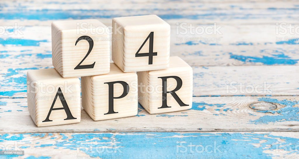 April 24th. Wooden cubes with date of 24 April  on old blue wooden background. stock photo