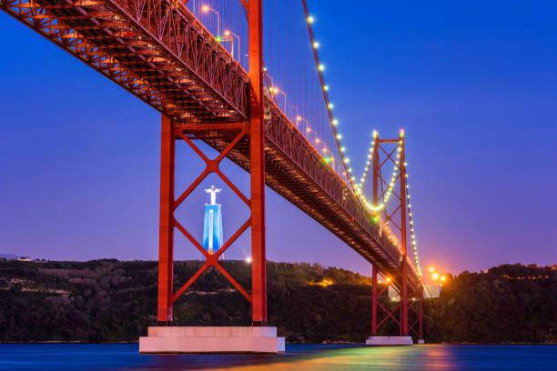 25 de abril Bridge e Cristo Rei estátua em Lisboa Portugal ao pôr do sol - foto de acervo